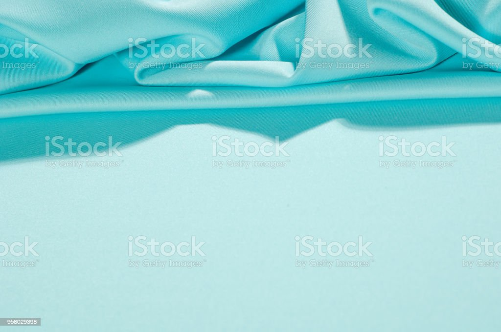 Texture. Background. Template. Pamper your design with a luxurious light blue silk flag. The blue dip can boast of a dull sheen and a crisp hand. His stiff drape creates volume when he falls. stock photo