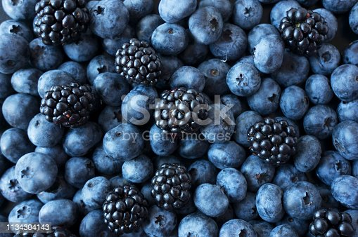 Texture berries close up. Top view. Black and blue berries. Ripe blueberries and blackberries. Various fresh summer berries. Mix berries.