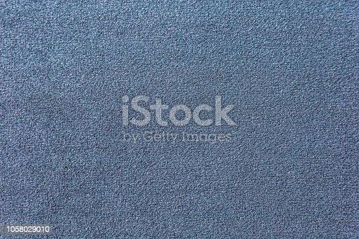 Texture of a dark blue carpet. Close-up of gradient light.