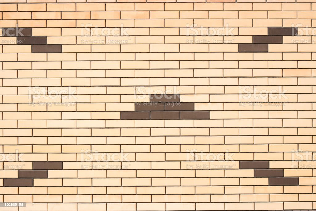 Texture of a wall of yellow brick with a pattern stock photo