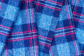 Traditional fall fashion. The background and texture of a classic woolen autumn scarf or blue plaid. Beauty and home comfort