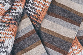 Traditional fall fashion. The background and texture of a classic woolen autumn scarf or brown plaid. Beauty and home comfort