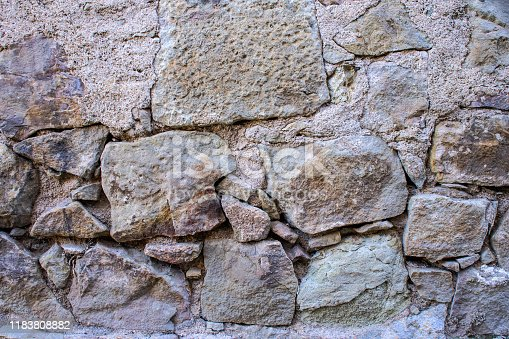 973649382istockphoto A texture of an old grey stone wall with concrete and big and small stones 1183808882