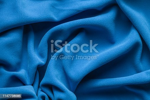 Background texture of bright blue fleece, soft napped insulating fabric made of polyester, wavy pattern