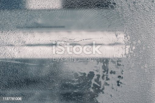 The texture of broken glass; close-up view of a broken windshield with a blurry background behind and muddy right part since water got into the triplex