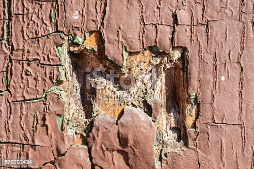 894368086 istock photo Texture Of Brown And Cyan Cracked Paint On Wooden Wall With Letter