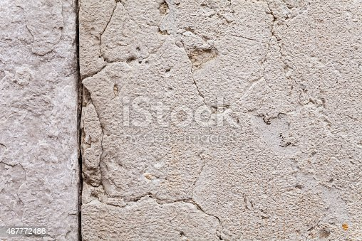 Close up on the texture of cracks and crevices in an ancient, sun-withered stone wall. Two-dimensional surface structure for use as solid background. Outdoor shot with camera mounted on tripod.