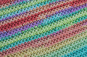 Texture of crocheted fabric from multi-colored yarn. Traditional hobby.