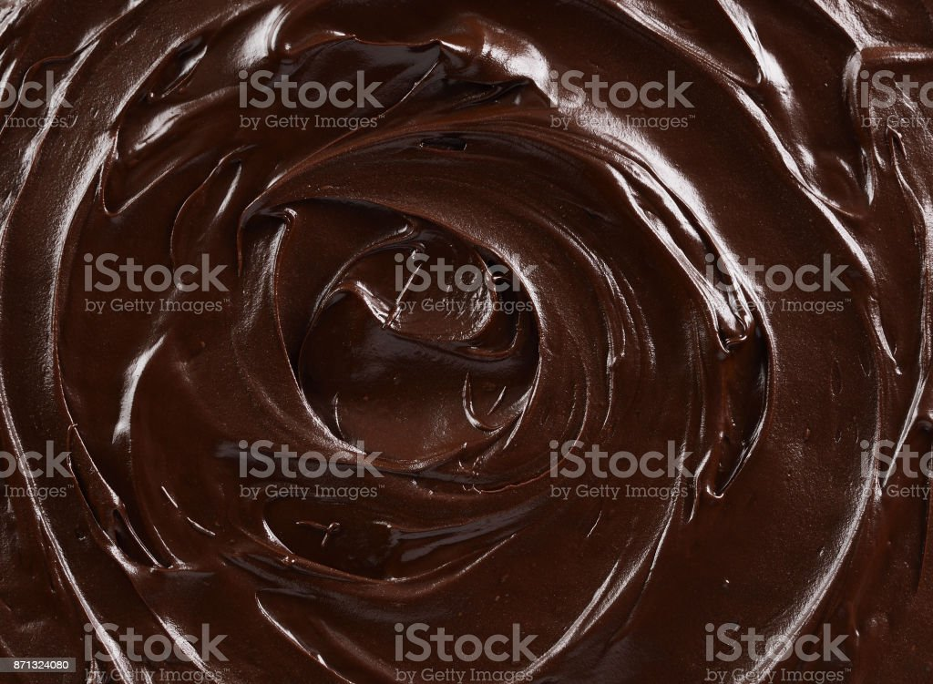 Texture of dark chocolate icing swirl close up. Food background stock photo