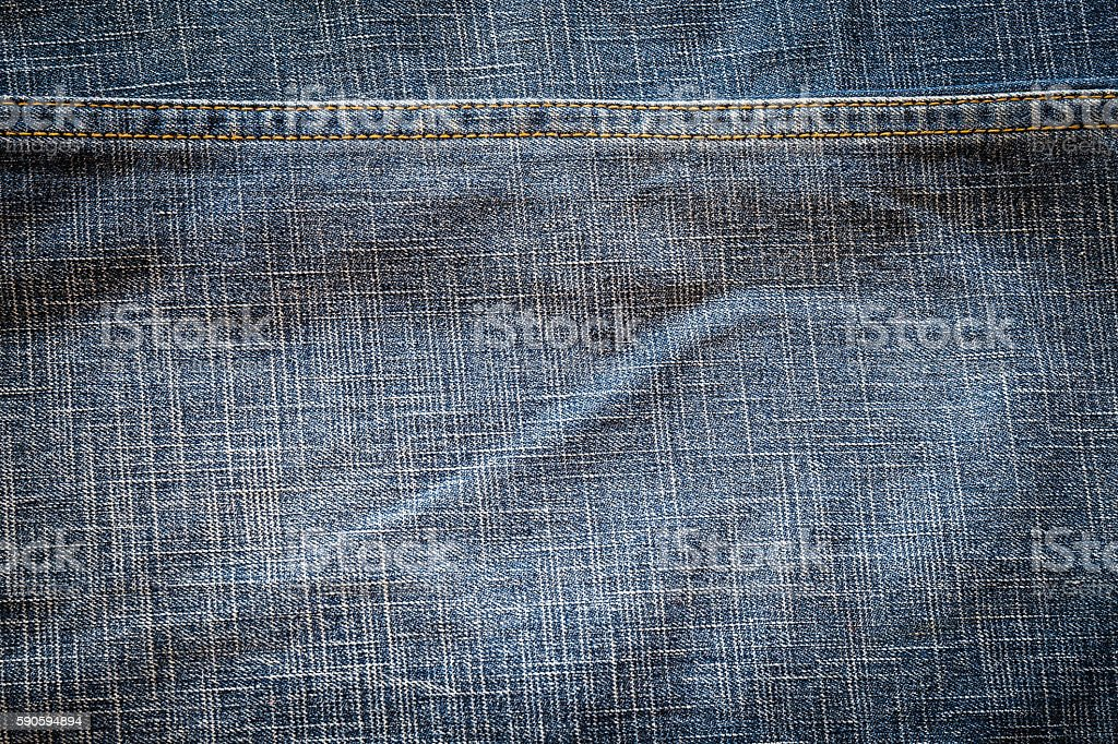 Texture of dark fabric blue jeans textile with seam. stock photo