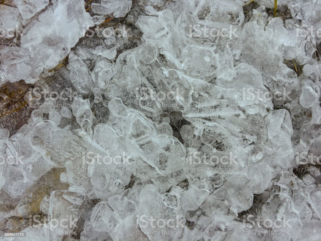 Texture of frozen sheet of ice forming on surface of flowing cold river water during winter stock photo