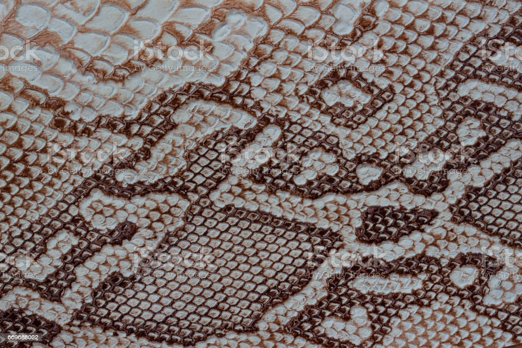 Texture of genuine leather close-up, embossed under the skin a reptile, with fashion pattern and matte surface. Natural shades, trendy background stock photo