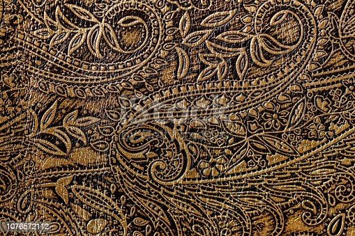 Texture of golden brown genuine leather close-up, with embossed floral trend pattern, wallpaper or banner design. With place for your text