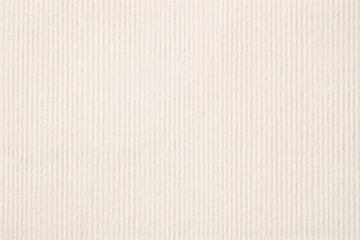 Texture of cream-coloured pastel paper with small inclusions for watercolor and artwork. Modern background, backdrop, substrate, composition use with copy space