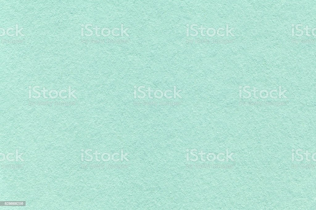 Texture of old light cyan paper background, closeup. Structure of dense turquoise cardboard
