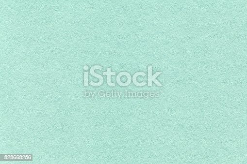 istock Texture of old light cyan paper background, closeup. Structure of dense turquoise cardboard 828668256