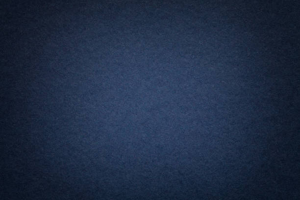 Texture of old navy blue paper background, closeup. Structure of dense cardboard. Texture of vintage dark denim paper background with vignette. Structure of dense navy blue kraft cardboard with frame. Felt gradient backdrop closeup. dark blue stock pictures, royalty-free photos & images