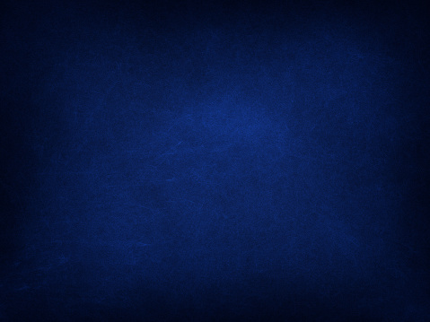 Texture of old navy blue paper background, closeup. Structure of dense cardboard.