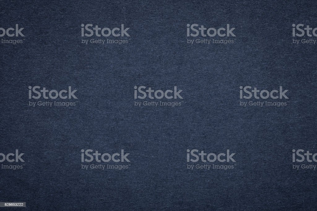 Texture of old navy blue paper background, closeup. Structure of dense dark denim cardboard stock photo