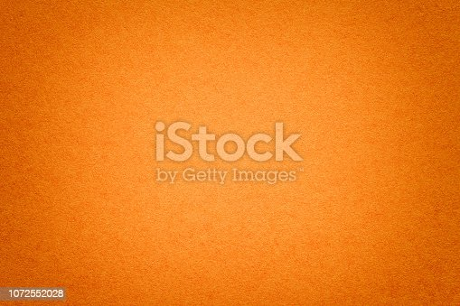 istock Texture of old orange paper background, closeup. Structure of dense cardboard. 1072552028