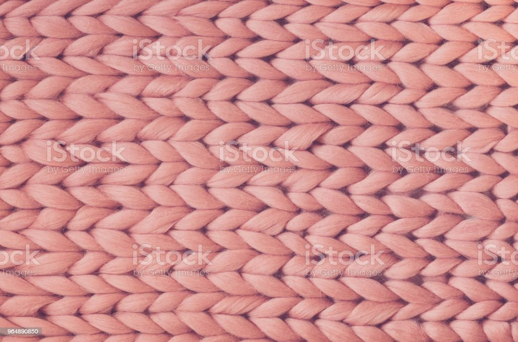 Texture of pink knit blanket. Large knitting. Plaid merino wool. Top view royalty-free stock photo