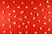 istock Texture of salted popcorn on a red background. Top view of popcorn texture background. 1273521415