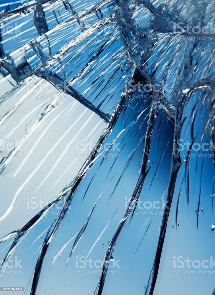 texture of shiny blue mirror surface with small and large cracks stock photo