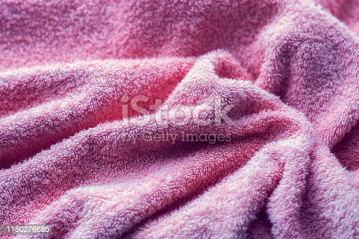 1151113068 istock photo Texture of soft tissue fibers. Close-up.Fluffy Gentle baby fabric with waves and folds. Soft pastel textile texture. Folds on the soft fabric. Rose towel terry cloth. 1150276685