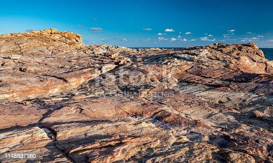 Texture of strange boulder rocks dark nook and warm color with sun lighting.