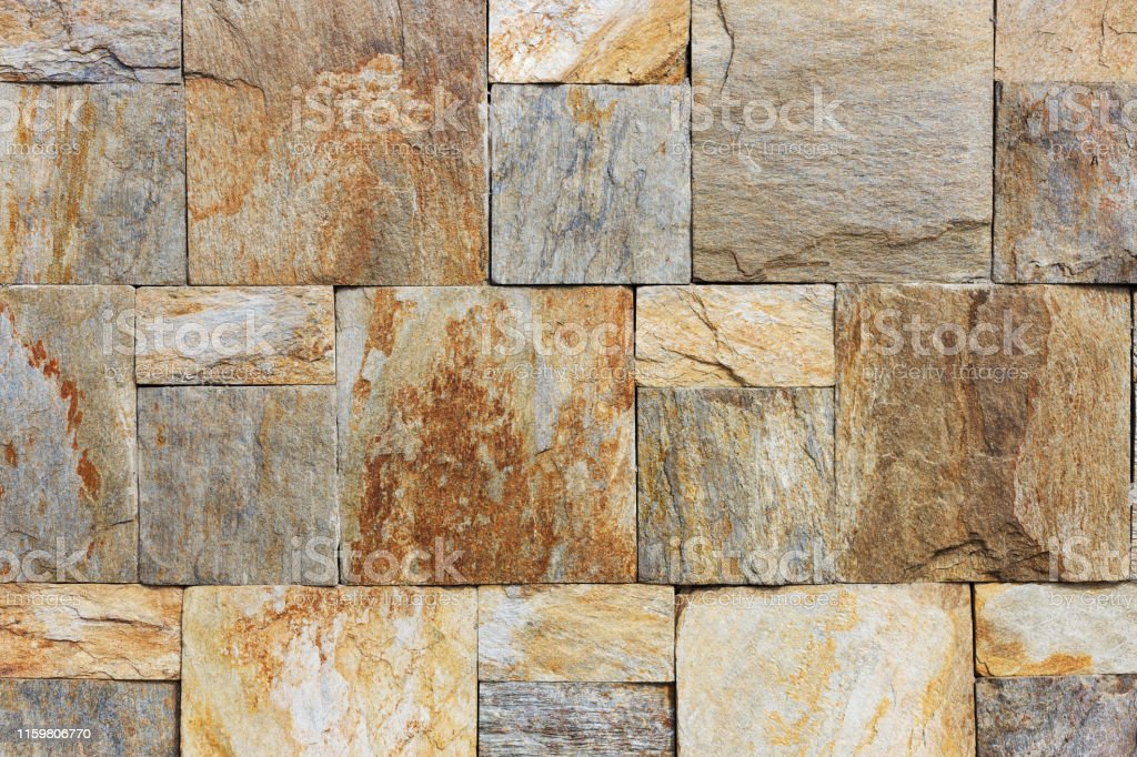 Texture of the brown and grey wall made of square stone tile bricks