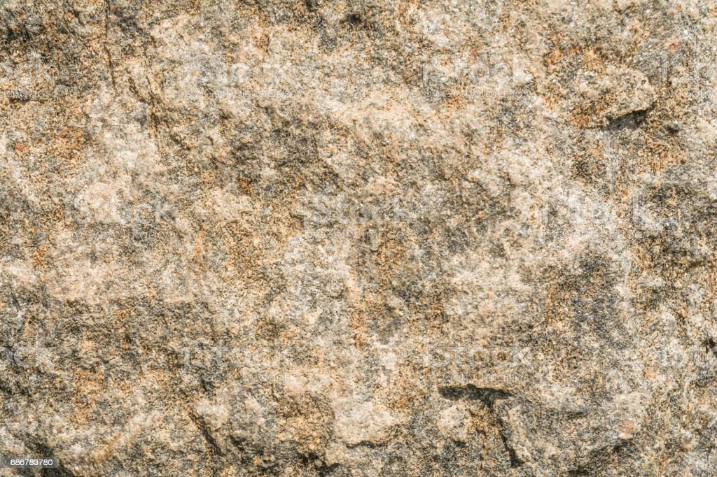 Texture of the surface of an antique stone wall under natural light by sunlight, abstract background stock photo