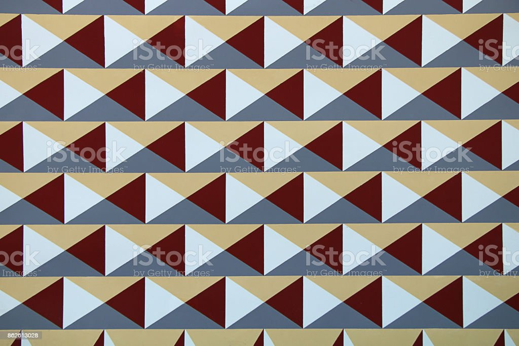 Texture of the wall with an unusual pattern. Geometrical figures in the form of triangles and envelopes painted on the wall. stock photo