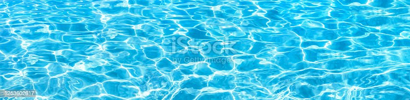 Shining blue water ripple background. Surface of water in swimming pool. Tropical beach water background.
