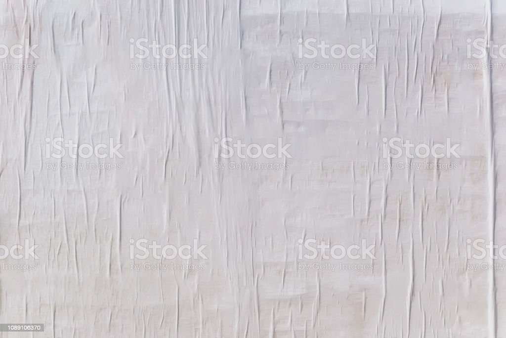 Texture of wet white folded paper on an outdoor poster wall, crumpled paper background royalty-free stock photo