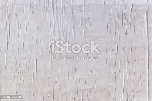 Texture of wet white folded paper on an outdoor poster wall, crumpled paper background.