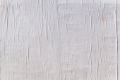 istock Texture of wet white folded paper on an outdoor poster wall, crumpled paper background 1089106370