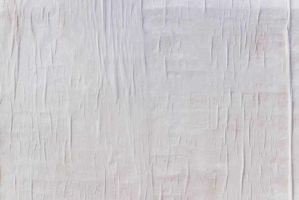 Texture of wet white folded paper on an outdoor poster wall, crumpled paper background stock photo