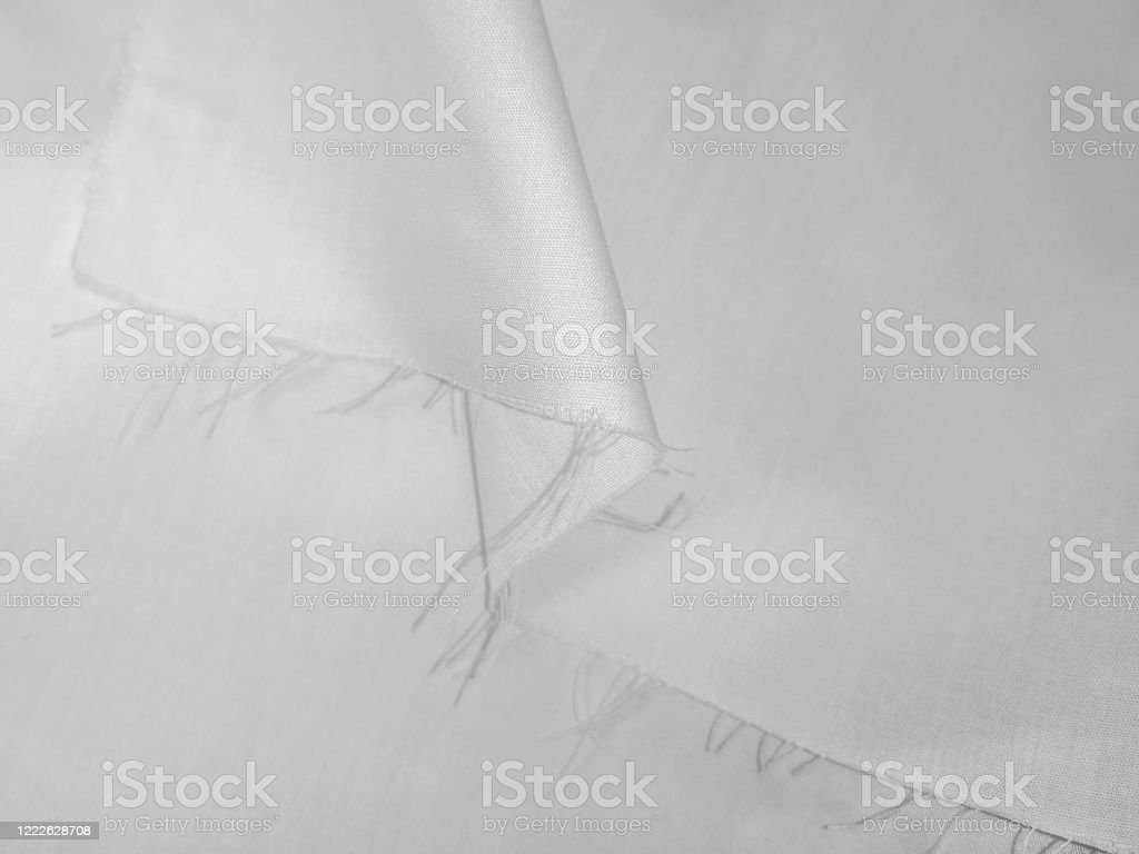 Texture of white fabric with a fringe on a cut edge Texture of white fabric with a fringe on a cut edge. Textile background with fold, close-up Abstract Stock Photo