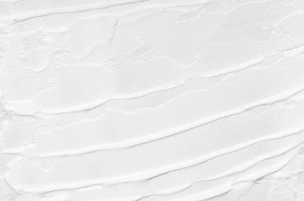 Texture of white face cream smeared on a white background. Cosmetic texture, face and body care. stock photo