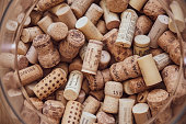 Wine corks texture closeup framed by blurry glass edges of round vase. Stack of various wine bottle stoppers for alcohol concept background