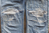 Close-up background, leg surface, torn old jeans, which have been sewn repaired.
