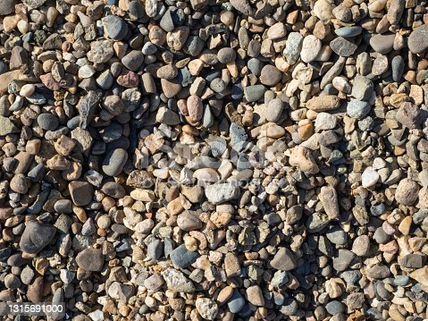 Textured background of colorful gravel stones. Empty space to insert.