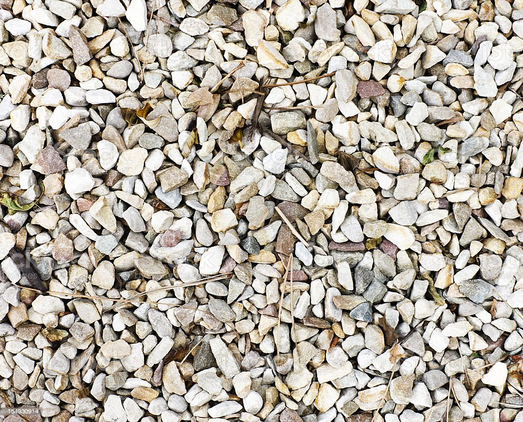 Textured background of pale gravel chips with scattered dry stalks stock photo