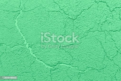 istock Textured background yellow clay cracked plaster. Wall background. 1285648930