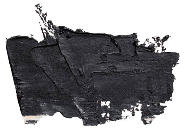 Textured black oil paint brush stroke, isolated on white background.
