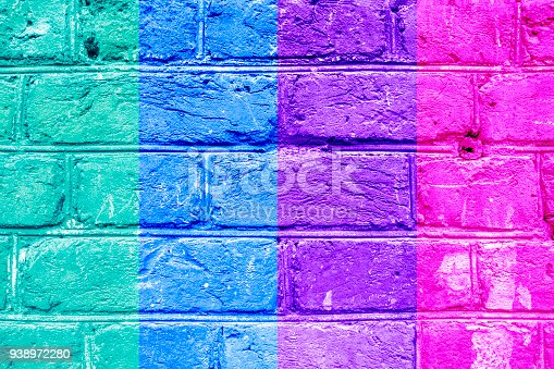 istock Textured brick wall with bright multicolored vertical stripes of green, blue, vilet and pink, abstract background. Concept of graphite walls, urban culture, aerosol pictures. 938972280