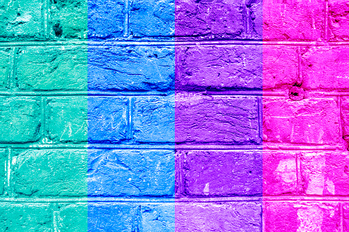 Textured brick wall with bright multicolored vertical stripes of green, blue, vilet and pink, abstract background. Concept of graphite walls, urban culture, aerosol pictures.