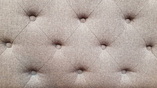 Textured fabric surface of upholstered furniture. Rhombus pattern of grey sofa tightened with round buttons on soft textile background. Interior upholstery backdrop. stock photo