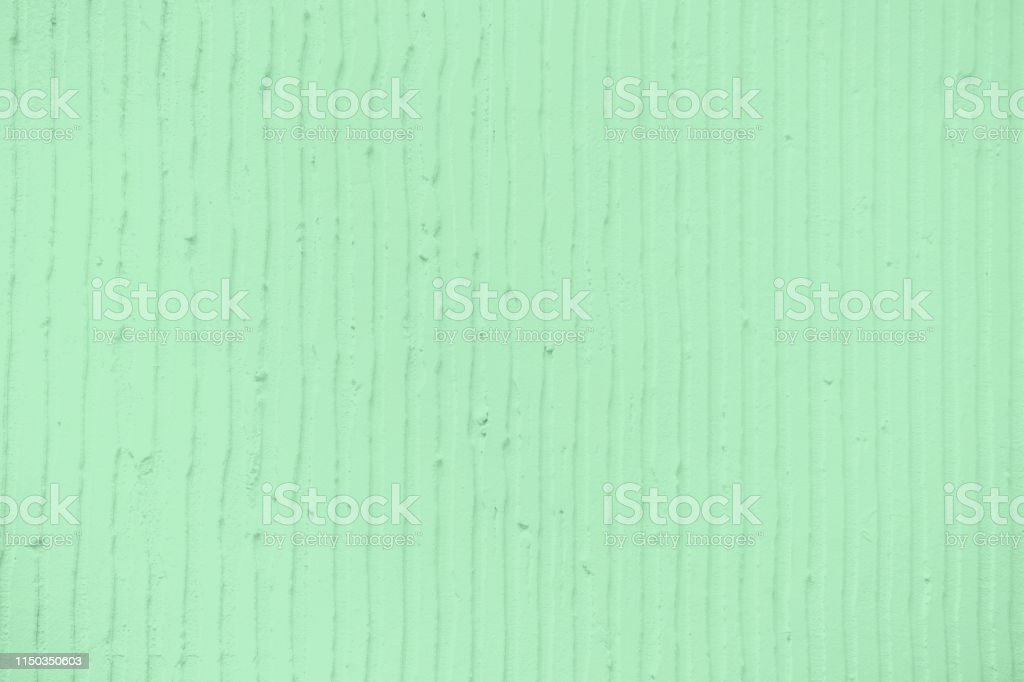 Closeup of the wall with a decorativetrendy colored mint plaster...