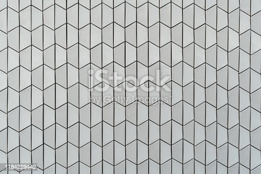 A frontal view of a modernbright ceramic or stone texture consisting of vertically placed trapezes; an evenly lit textured wall outdoors in Belem district of Lisbon, Portugal